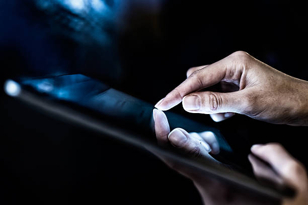 Closeup of woman holding a digital tablet in the dark hand presses on screen digital tablet male animal stock pictures, royalty-free photos & images