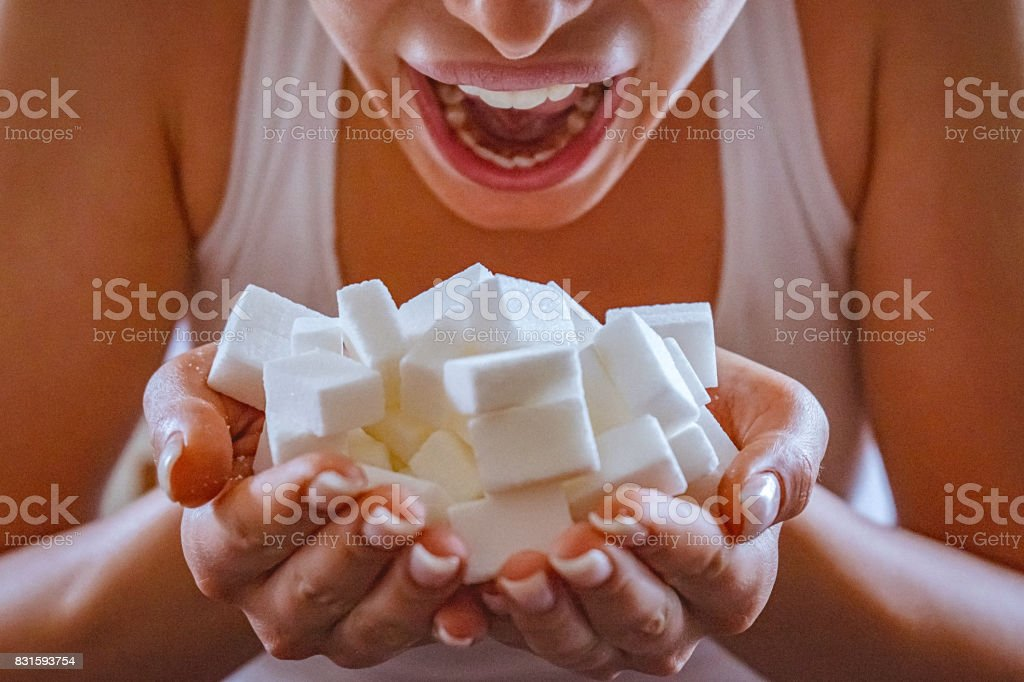 Close-up of woman holding a hands full of sugar cubes in front of her open mouth stock photo