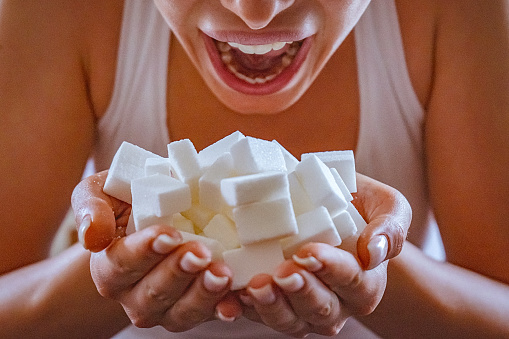 Closeup Of Woman Holding A Hands Full Of Sugar Cubes In Front Of Her Open Mouth - Fotografie stock e altre immagini di Accudire