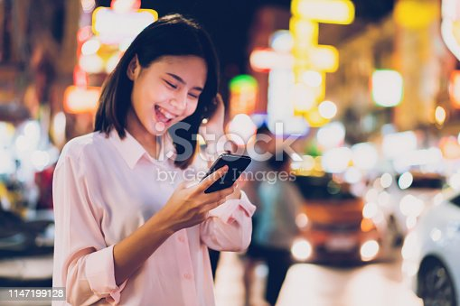 istock Closeup of woman holding a smartphone at night on city shopping street, and people walk. Technology for communication concept. 1147199128