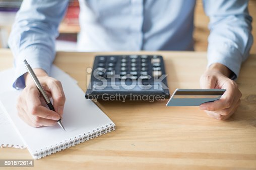 645670208istockphoto Closeup of Woman Holding Credit Card and Writing 891872614