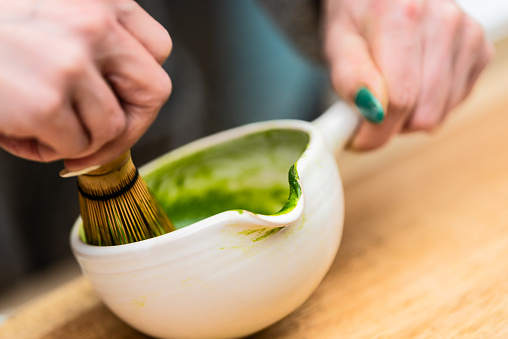 Closeup of woman holding Japanese tea cup teapot pot and whisk on table making, stirring and preparing koicha matcha hot drink