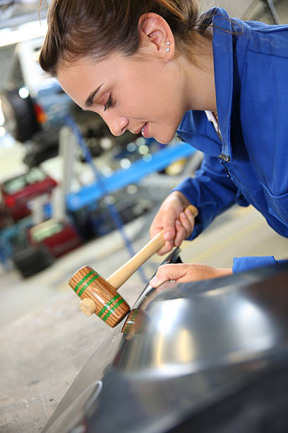 Closeup of woman holding mallet in auto shop stock photo