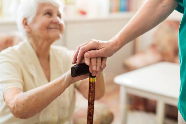 Nahaufnahme der Frau, die die Hände des Senior auf Rohre lehnt – Foto