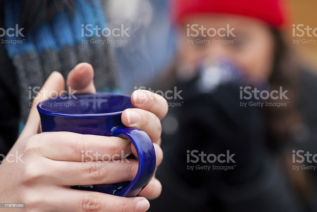 Closeup of woman holding steaming mug of coffee outdoors royalty-free stock photo