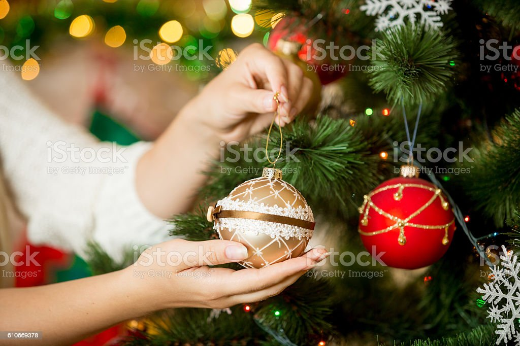 Closeup of woman in sweater decorating Christmas tree with baubles stock photo