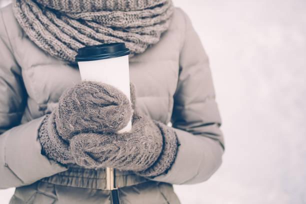 在冬季公園裡抱著帶走的咖啡, 穿著保暖夾克的婦女特寫。穿著圍巾和手套的微笑的女人。她在戶外度過閒置時間。溫飲理念 - 冬天大衣 個照片及圖片檔