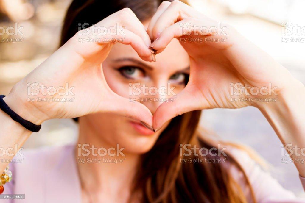 Primer plano de mujer haciendo un símbolo en forma de corazón con las manos foto de stock libre de derechos