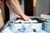 Close-up of woman organizing her luggage at hotel room
