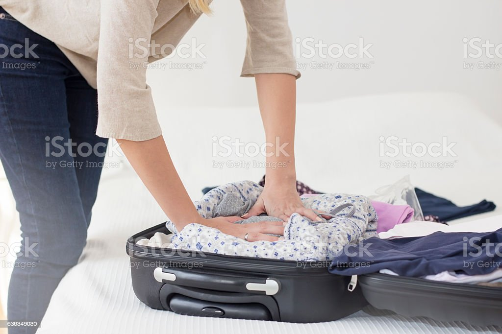 Close-up of woman packing a suitcase stock photo