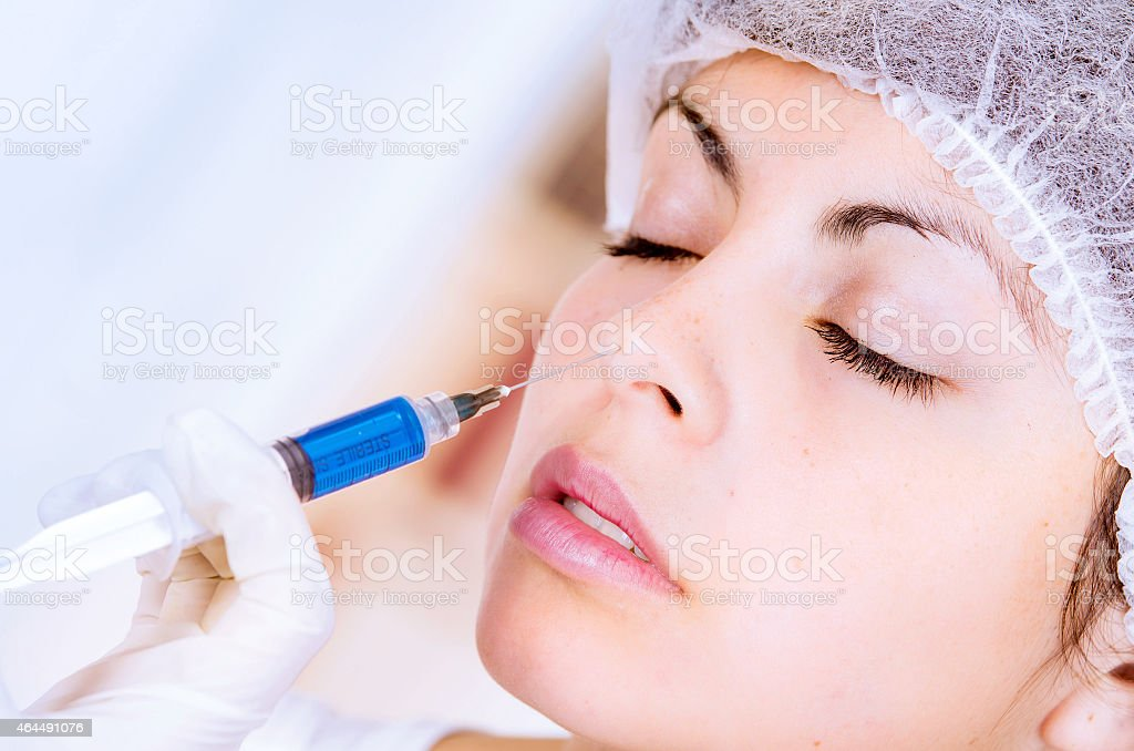 closeup of woman receiving cosmetic injection through nose stock photo