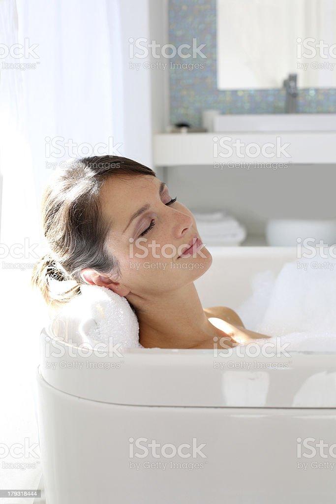 Closeup of woman resting in a big bathtub stock photo
