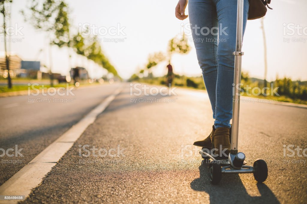 Close-up of woman riding push scooter stock photo