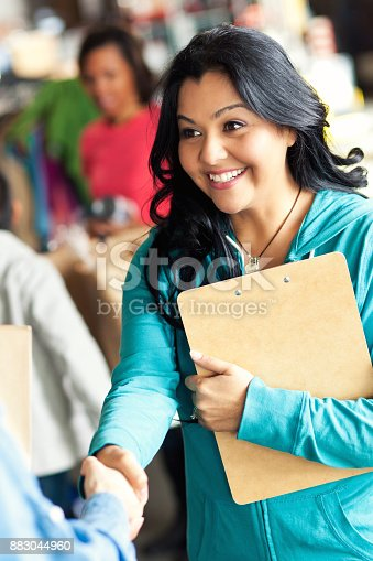 istock Closeup of woman shaking hands during food bank drive 883044960