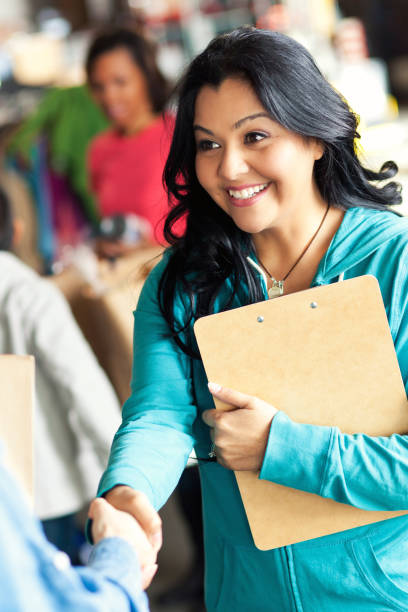 Closeup of woman shaking hands during food bank drive stock photo