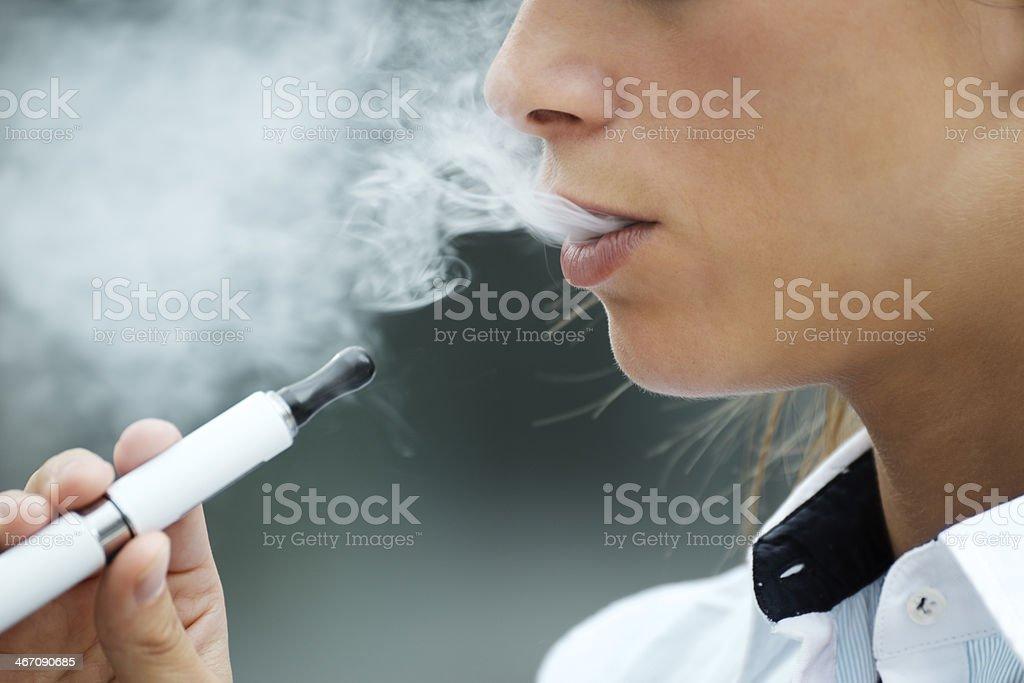 Primer plano de mujer fumando cigarrillo electrónico al aire libre - Foto de stock de 20 a 29 años libre de derechos