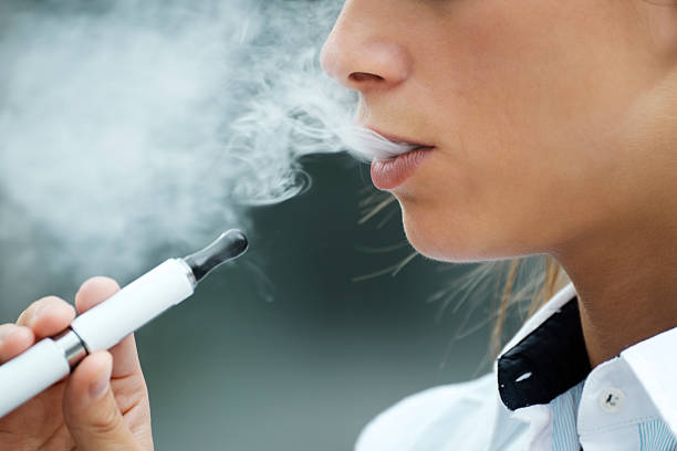 closeup of woman smoking electronic cigarette outdoor closeup of woman smoking e-cigarette and enjoying smoke. Copy space electronic cigarette stock pictures, royalty-free photos & images