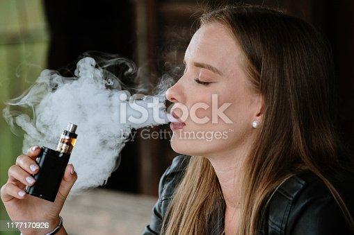1033177506 istock photo Closeup of woman smoking electronic cigarette 1177170926