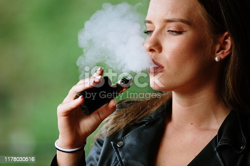 1033177506 istock photo Closeup of woman smoking electronic cigarette 1178030516