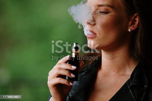 1033177506 istock photo Closeup of woman smoking electronic cigarette 1178933601