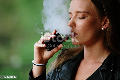 1033177506 istock photo Closeup of woman smoking electronic cigarette 1178933637