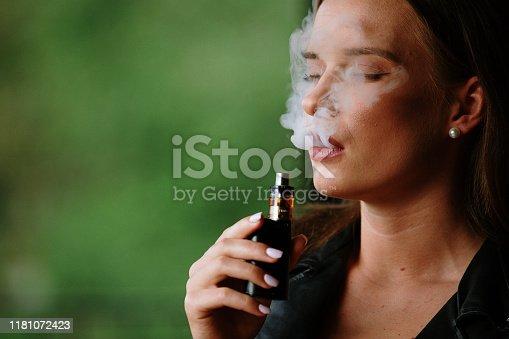1033177506 istock photo Closeup of woman smoking electronic cigarette 1181072423