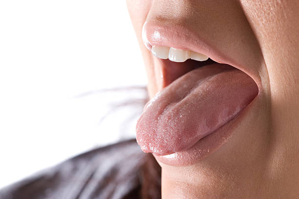 close-up of woman sticking out her tongue - human saliva stock pictures, royalty-free photos & images