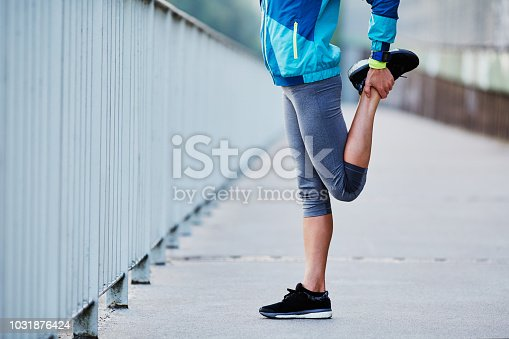 Close-up of woman stretching legs while morning running