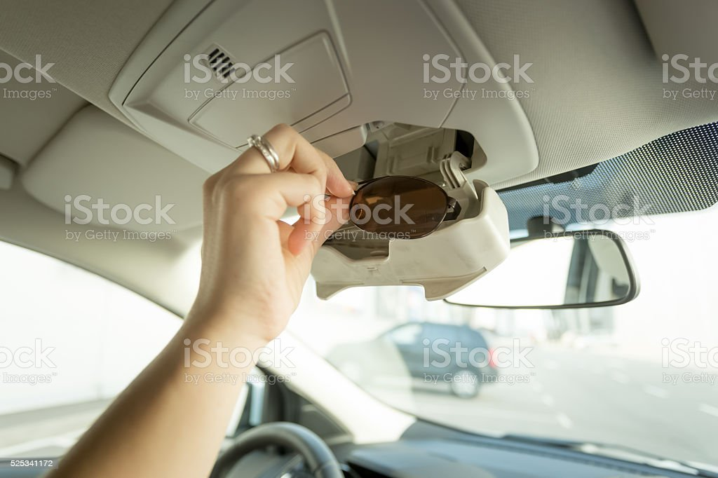 Closeup of woman taking sunglasses out of special car compartmen stock photo