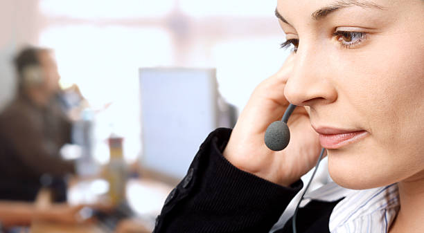 Closeup of woman touching her headset and looking down stock photo