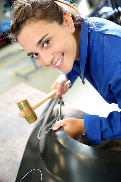 Closeup of woman using a mallet in garage stock photo