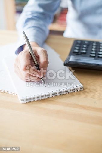 645670208istockphoto Closeup of Woman Using Calculator and Writing 891872602