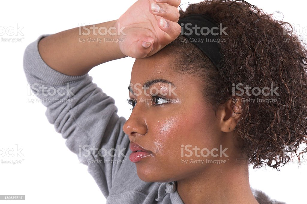 Close-up of woman wiping sweaty forehead after a workout stock photo