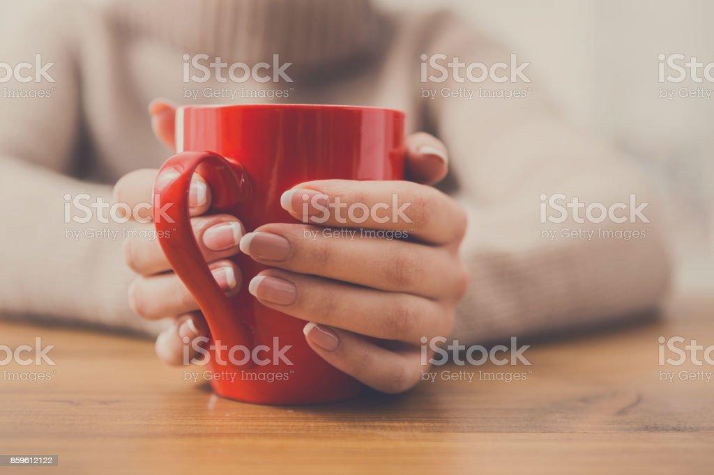 Primer plano de mujer con la taza de bebida caliente - foto de stock