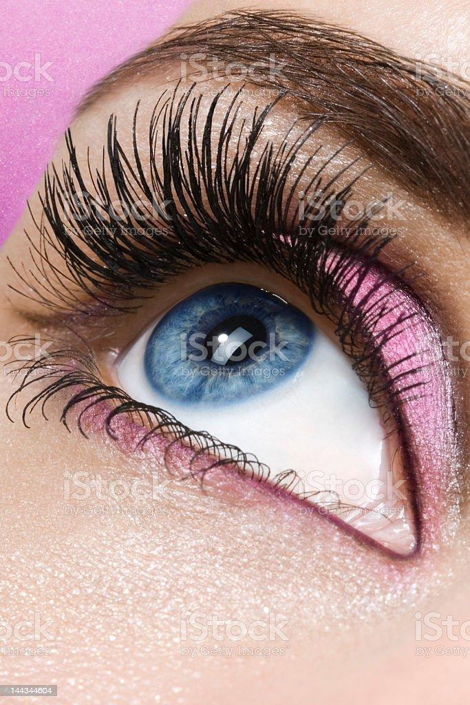 Closeup of woman's eye wearing pink eye shadow royalty-free stock photo