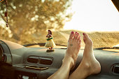 Close-up of woman's feet on dashboard of mini van