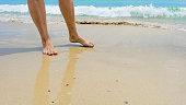 Closeup of woman's feet walking on the beach during a golden sunset