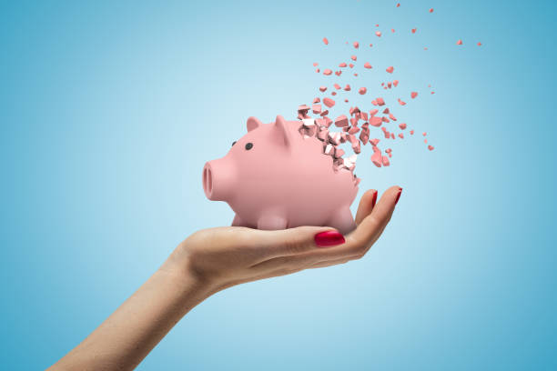 Close-up of woman's hand facing up and holding cute pink piggy bank that has started to disintegrate into pieces on light-blue background.