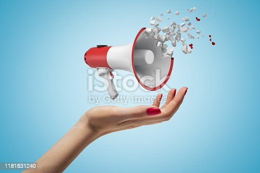 903659714istockphoto Close-up of woman's hand facing up and levitating megaphone that has started to disintegrate into pieces on light-blue background. 1181831240