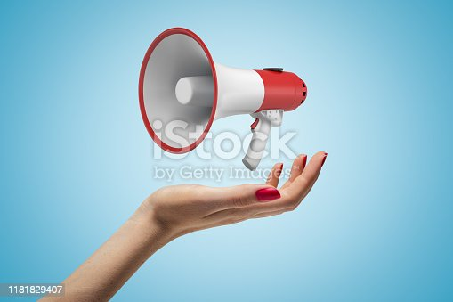 903659714istockphoto Close-up of woman's hand facing up and levitating red and white megaphone on light-blue background. 1181829407