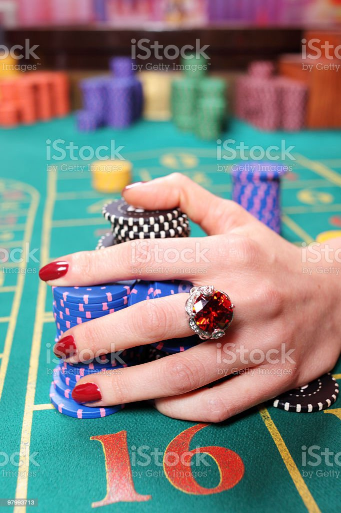 Close-up of woman's hand handling a big  gambling pile. royalty free stockfoto