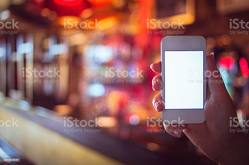 Close-up of woman's hand holding smartphone over the blurred background stock photo