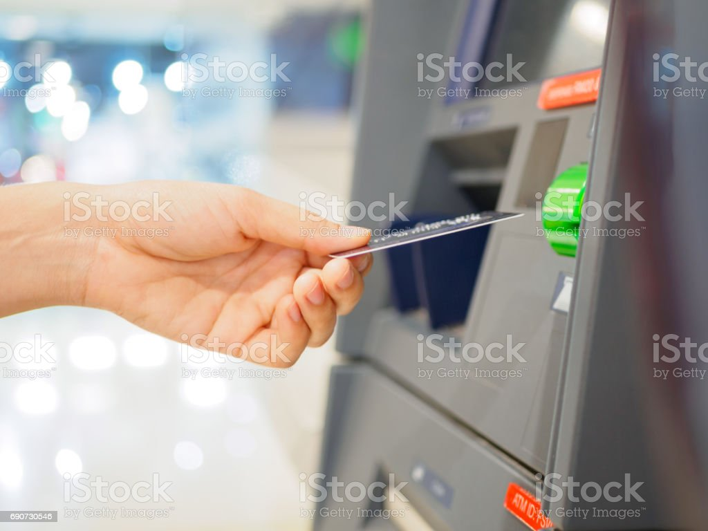 Close-up of woman's hand inserting debit card into an ATM machine. Horizontal shot. – zdjęcie