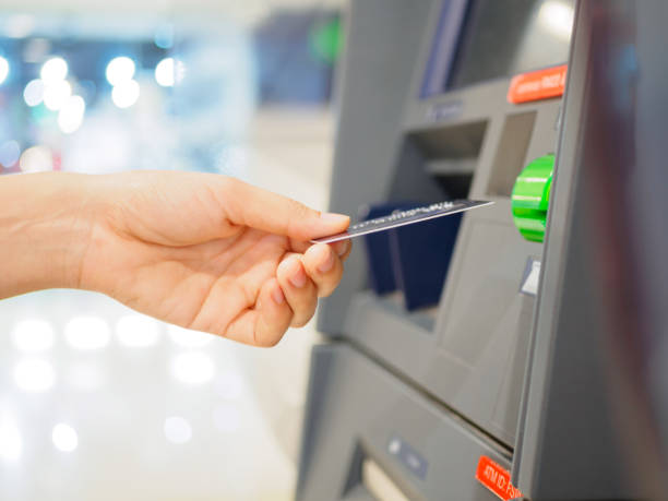 Close-up of woman's hand inserting debit card into an ATM machine. Horizontal shot. - foto de stock