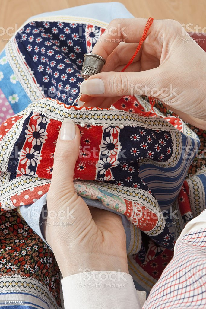 Close-up of woman's hand stitching quilting stock photo