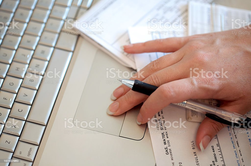 Close-up of woman's hand using trackpad to pay bills online royalty-free stock photo