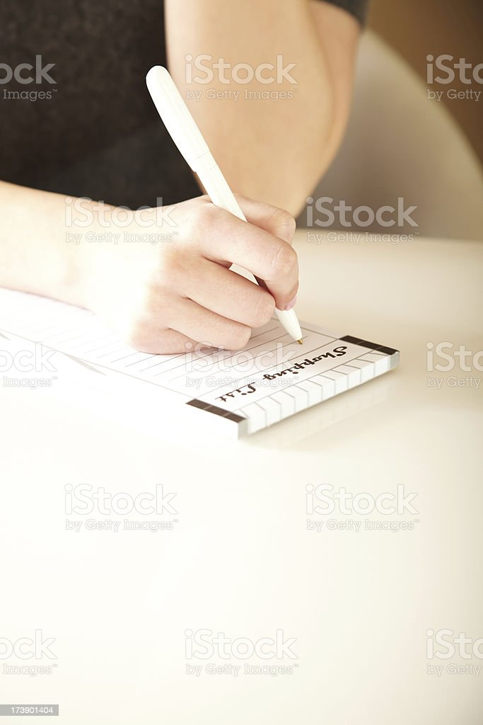 Close-up of Woman's Hand Writing in a Notepad royalty-free stock photo