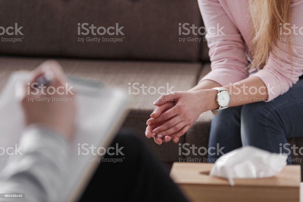 Nahaufnahme von Frauenhand während Beratung treffen mit einem professionellen Therapeuten. Feld von Geweben und eine Hand des Beraters verschwommen in der Front. Lizenzfreies stock-foto