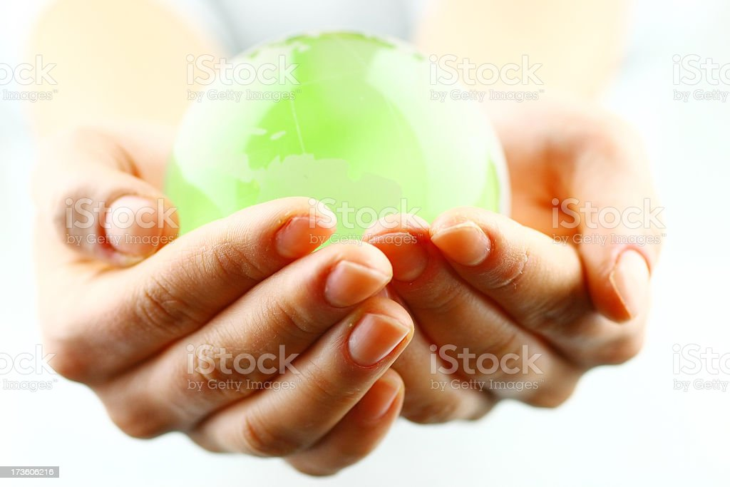 Close-up of woman's hands holding a bright green globe royalty-free stock photo