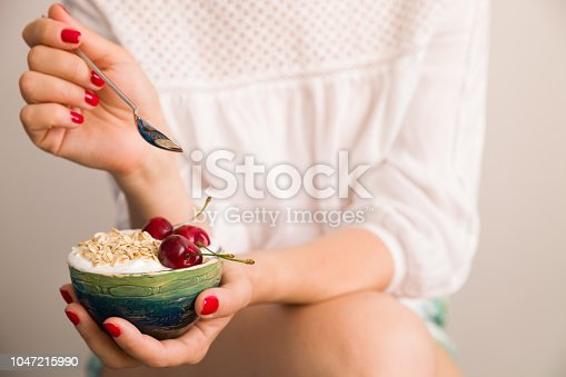 istock Closeup of woman's hands holding a cup with organic yogurt with oats and cherries. Homemade vanilla yogurt in girl's hands. Breakfast or snack. Healthy eating and lifestyle concept. 1047215990